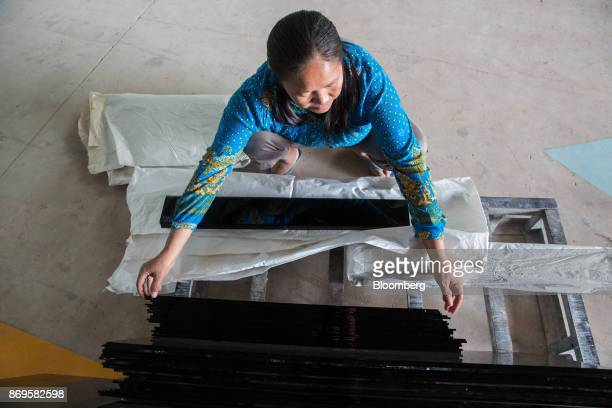 A worker handles a sheet of glass in the packaging department at the Somvang Glass Factory on the outskirts of Vientiane Laos on Wednesday Nov 1 2017...