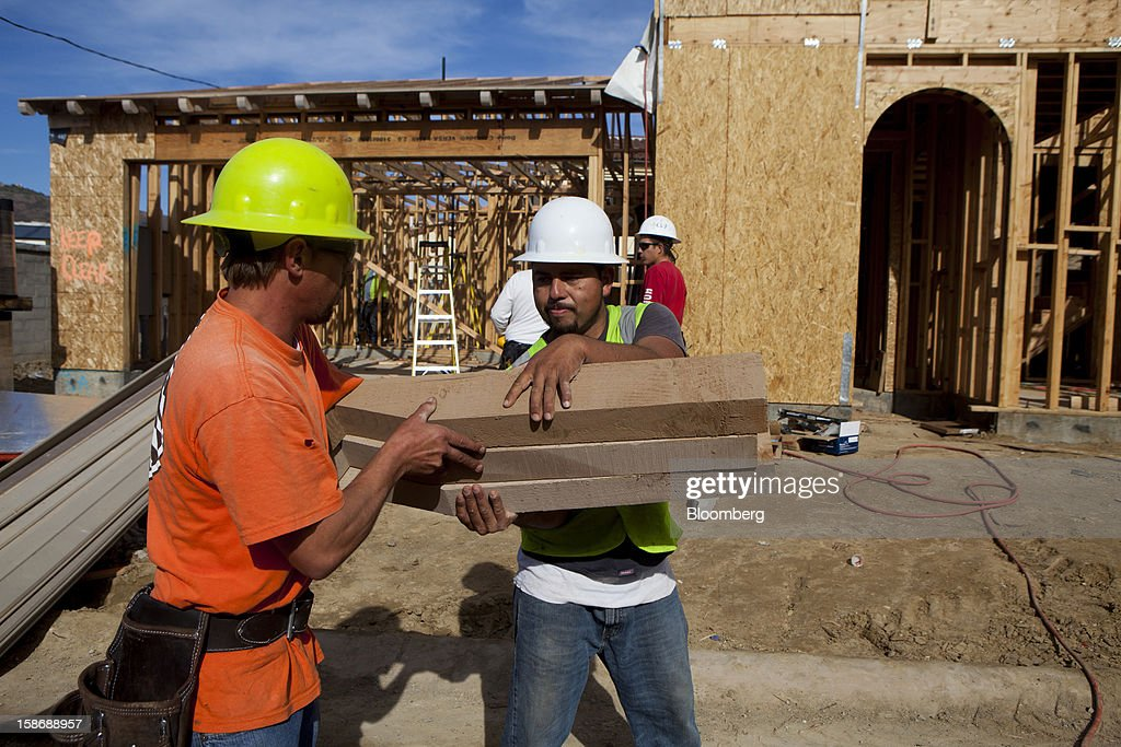 A worker hands his colleague a stack of lumber outside a house under construction at Davidson Communities LLC's Arista at The Crosby development in Rancho Santa Fe, California, U.S., on Friday, Dec. 21, 2012. New home sales climbed to a 380,000 annual rate in November, the most since April 2010, according to the median forecast of 60 economists surveyed by Bloomberg before Dec. 27 figures from the Commerce Department. Photographer: Sam Hodgson/Bloomberg via Getty Images