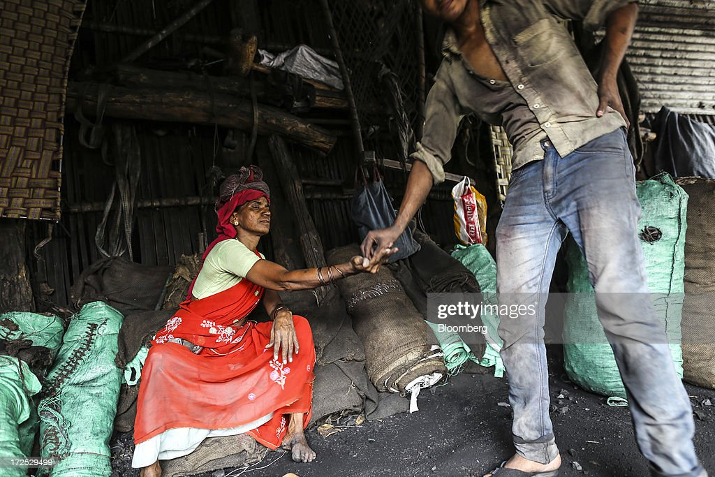 A worker hands some tobacco to another worker during a break at a coal wholesale market in Mumbai, India, on Tuesday, July 2, 2013. India, the worlds third-largest coal consumer, imported 43 percent more of the fuel than a year ago on increased demand from power stations and steelmakers, according to shipping data, and is set to eclipse China as the top importer of power station coal by 2014. Photographer: Dhiraj Singh/Bloomberg via Getty Images