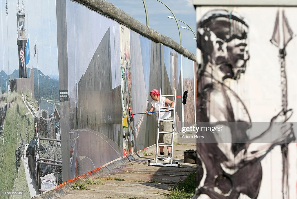 A worker hangs a photo for the 'Wall on Wall' exhibition at the East Side Gallery section of the former Berlin Wall on July 10, 2013 in Berlin, Germany. A series of photos shot since 2006 by photographer Kai Wiedenhoefer hanging on the Western, river Spree side of the Wall features large pictures of separation barriers in Baghdad, Korea, Cyprus, Mexico, Morocco, Israel, Belfast, and in the former East Germany itself. The opposite side of the stretch of the original Wall is known as East Side Gallery, a memorial to peace and freedom covered in murals questioning the legacy of the original Wall, and the subject of several demonstrations earlier in March this year when a sections of it were threatened with removal to make way for a construction site for luxury apartment buildings, discussion of which is still ongoing with a decision expected to be reached in early August.