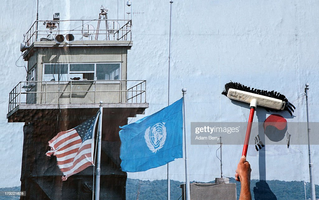 A worker hangs a photo of the North and South Korean border's Demilitarized Zone (DMZ) as part of the 'Wall on Wall' exhibition at the East Side Gallery section of the former Berlin Wall on July 10, 2013 in Berlin, Germany. A series of photos shot since 2006 by photographer Kai Wiedenhoefer hanging on the Western, river Spree side of the Wall features large pictures of separation barriers in Baghdad, Korea, Cyprus, Mexico, Morocco, Israel, Belfast, and in the former East Germany itself. The opposite side of the stretch of the original Wall is known as East Side Gallery, a memorial to peace and freedom covered in murals questioning the legacy of the original Wall, and the subject of several demonstrations earlier in March this year when a section of it were threatened with removal to make way for a construction site for luxury apartment buildings, discussion of which is still ongoing with a decision expected to be reached in early August.