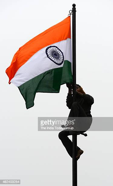 A worker hangs an Indian national flag on a pole prior to the arrival of US President Barack Obama in New Delhi