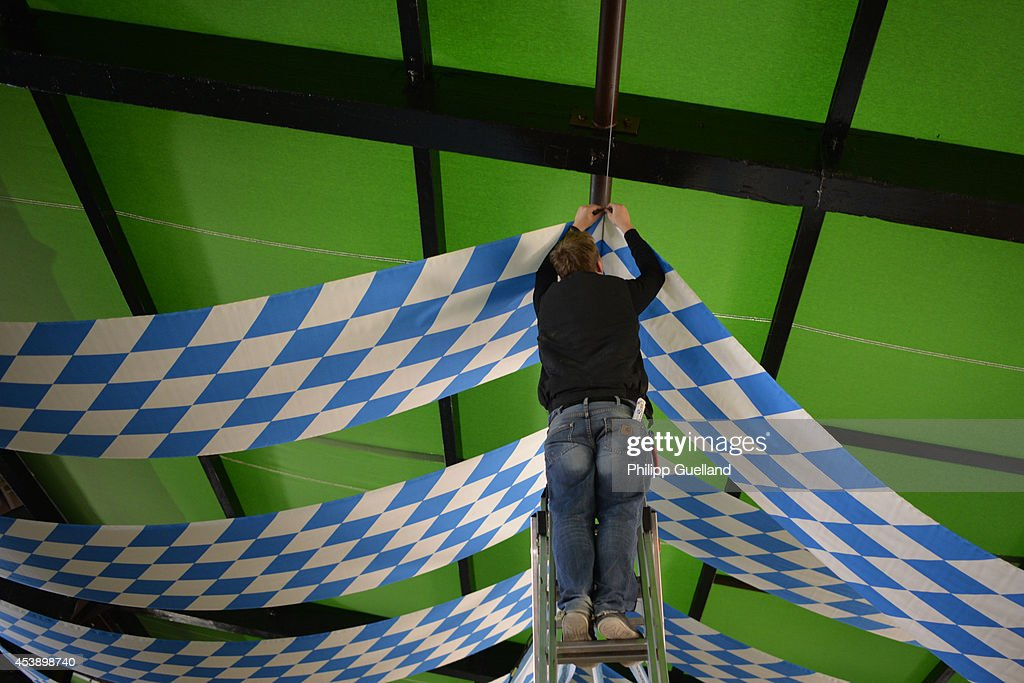 A worker hangs bavarian banners in a tent on the fairground four weeks ahead of Oktoberfest on August 21, 2014 in Munich, Germany. Munich Oktoberfest, which opens to the public on September 20, draws millions of visitors and is the biggest beer fest in the world. Photo by Philipp Guelland/Getty Images)