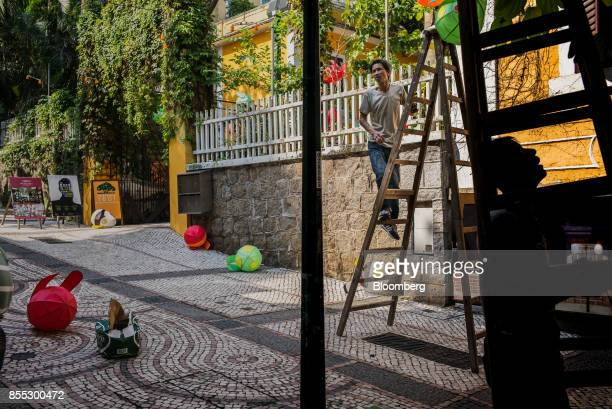 A worker hangs lantern decorations ahead of the midautumn festival in Macau China on Wednesday Sept 27 2017 Junkets flush with high rollers full...