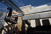 A worker hangs lights over the red carpet arrivals area as preparations continue for the 88th Annual Academy Awards at Hollywood Highland Center on...