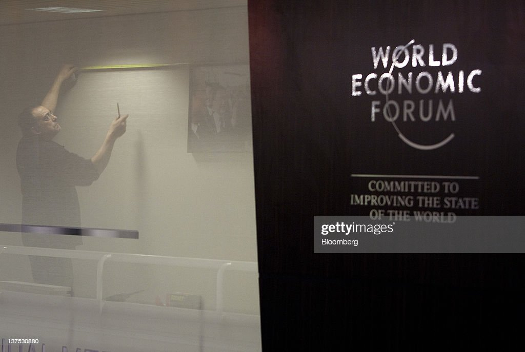 A worker hangs pictures inside the Congress Centre, the venue of the World Economic Forum's (WEF) 2012 annual meeting, in the town of Davos, Switzerland, on Sunday, Jan. 22, 2012. German Chancellor Angela Merkel will open next week's World Economic Forum in Davos, Switzerland, which will be attended by policy makers and business leaders including U.S. Treasury Secretary Timothy F. Geithner. Photographer: Scott Eells/Bloomberg via Getty Images