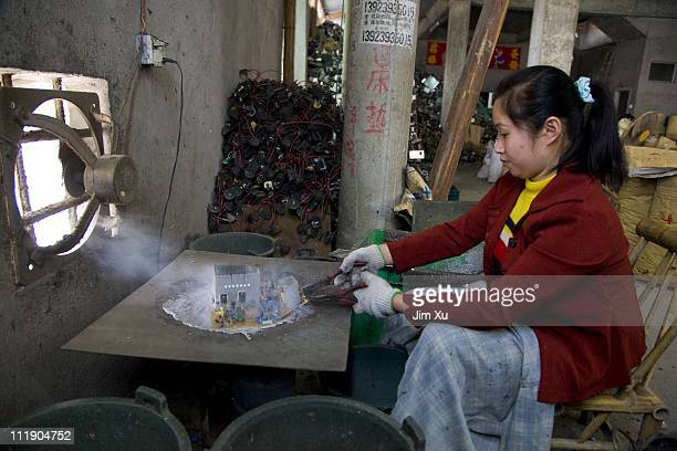 A worker heats up a computer board on a steel surface heated by charcoal to remove computer chips March 23 2008 in Guiyu China Since the late 1980's...