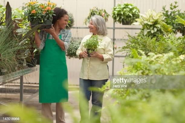 Worker helping customer in greenhouse