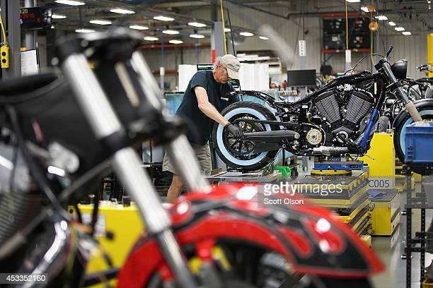 A worker helps to build a Victory motorcycle on the assembly line at the Polaris Industries factory on August 8 2014 in Spirit Lake Iowa Polaris...