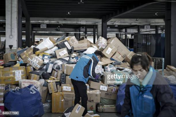 A worker holding a handheld scanner sorts through piled up packages at a ZTO Express Inc sorting facility in Shanghai China on Friday Feb 10 2017...