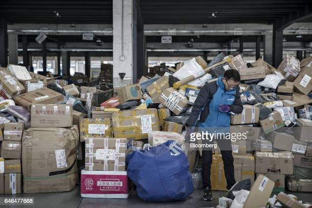 A worker holding a handheld scanner stands near piled up packages at a ZTO Express Inc sorting facility in Shanghai China on Friday Feb 10 2017...
