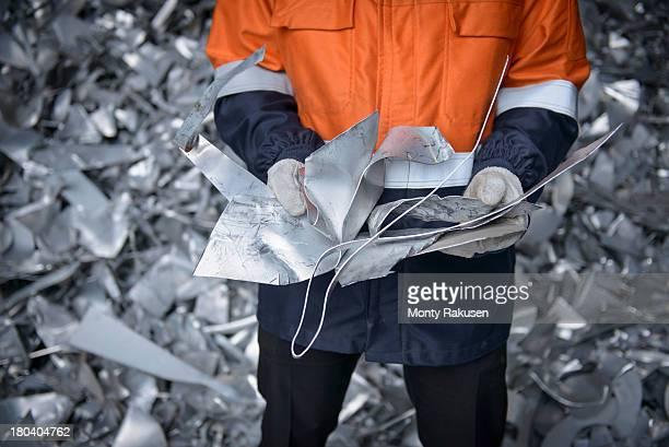 Worker holding aluminium scrap in aluminium recycling plant, close up