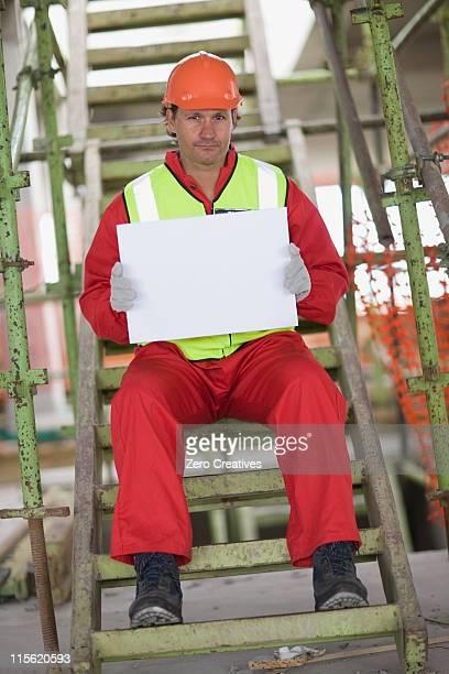 Lavoratore tenendo un vuoto foglio di carta
