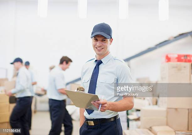 Worker holding clipboard in shipping area