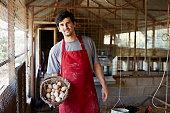 Worker holding egg basket at poultry farm