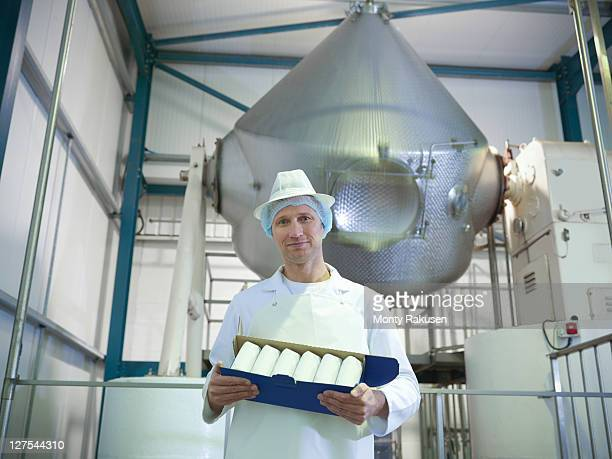 Worker holding goats butter in dairy