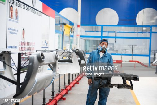 Worker holding machinery in manufacturing plant : Stock Photo