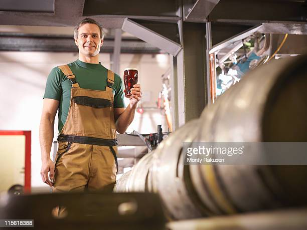 Worker holding pint of beer in brewery