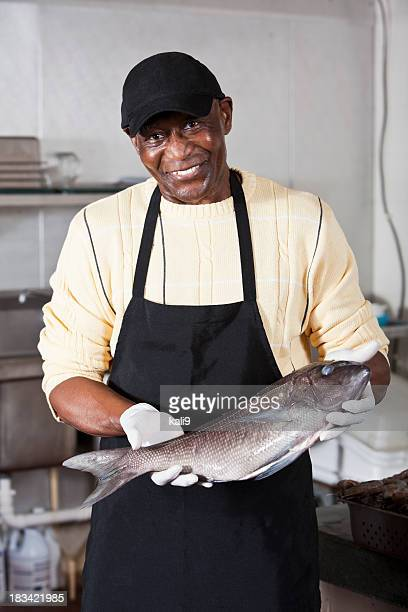 Worker holding seabass in fish market