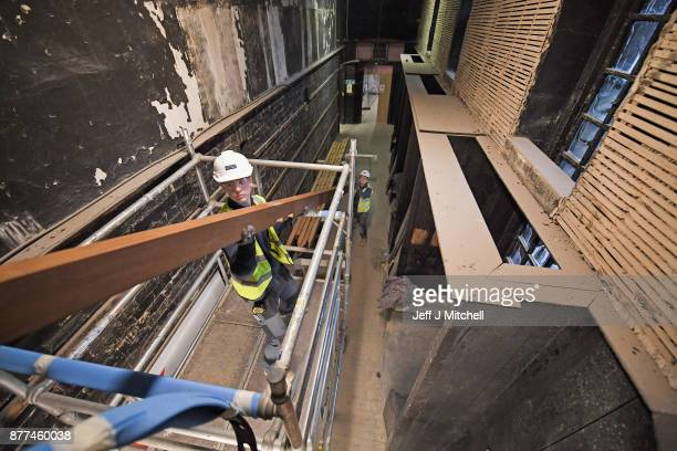 A worker holds a beam as specialist carpenters from Lawrence McIntosh install the floor to the bookstore above the Mackintosh Library on November 22...