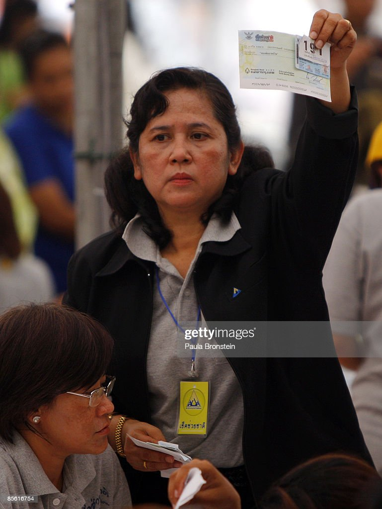 A worker holds a cheque up as thousands of Thais wait for hours to receive a government check of 2000-baht ($57.00 US) at the City hall March 26, 2009 in Bangkok, Thailand. The pay out is being given to stimulate an economy battered by the global financial crisis. Eight million Thais have been unemployed since September 1, 2008, and in total there are 9.4 million people who make less than 15000 baht per month and are eligible for the cash hand-out. Today 20,000 red-shirted protesters surrounded the prime minister's office demanding the government resign. The pro-Thaksin supporters claim that Prime Minister Abhisit Vejjajiva government came to power through illegal means and are demanding elections.