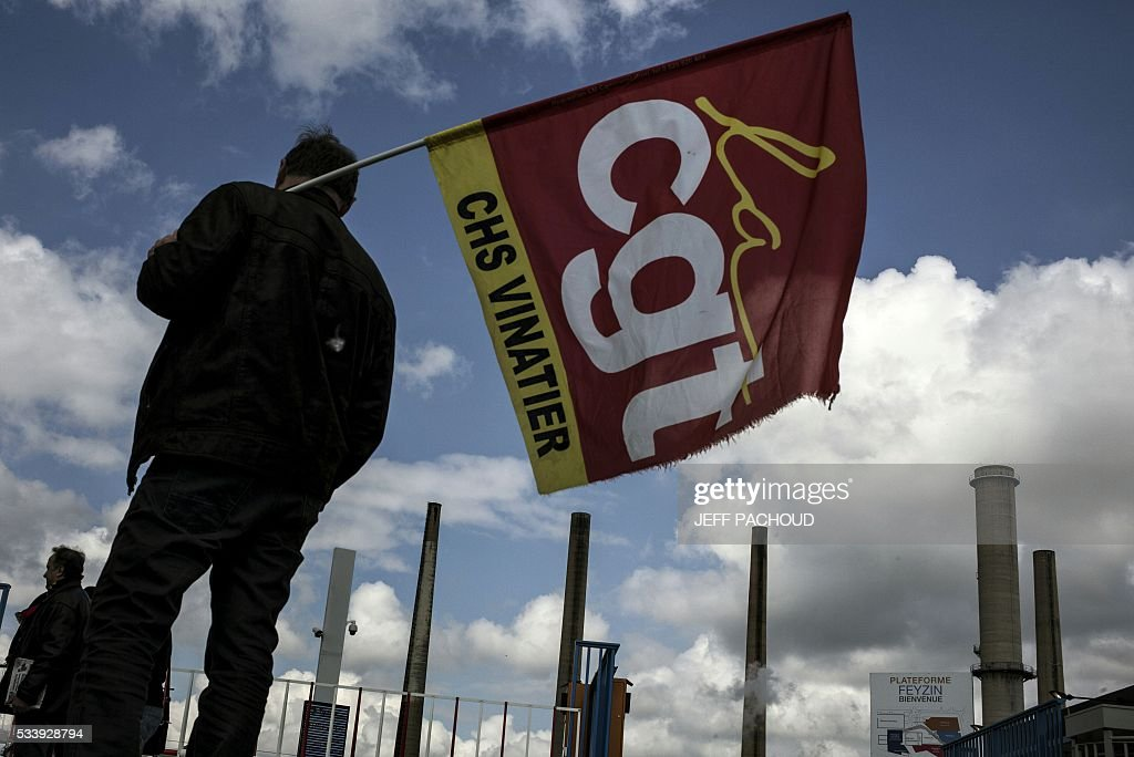 A worker holds a French CGT union flag in front of the Total oil refinery of Feyzin, near Lyon, central-eastern France, on May 24, 2016, during a strike at the plant to protest against government labour reforms. France's government stepped up efforts on May 24 to break blockades and strikes at refineries that are threatening to paralyse the country just three weeks ahead of the Euro 2016 football tournament. Six out of eight of the refineries in France have either stopped operating or have reduced output due to strikes and blockades. PACHOUD