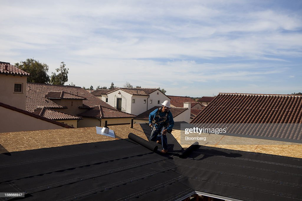 A worker holds a hammer as he unrolls roofing material on a house under construction at Davidson Communities LLC's Arista at The Crosby development in Rancho Santa Fe, California, U.S., on Friday, Dec. 21, 2012. New home sales climbed to a 380,000 annual rate in November, the most since April 2010, according to the median forecast of 60 economists surveyed by Bloomberg before Dec. 27 figures from the Commerce Department. Photographer: Sam Hodgson/Bloomberg via Getty Images