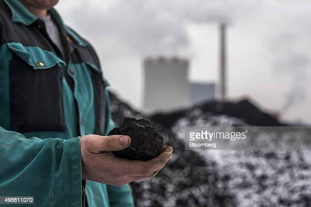A worker holds a lump of brown coal in this arranged photograph at the Bilina open pit lignite mine operated by Severoceske Doly AS a unit of CEZ AS...