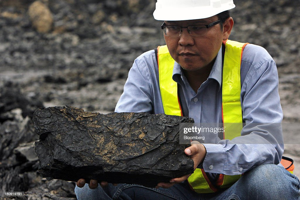 A worker holds a lump of coal for a photograph at the PT Exploitasi Energi Indonesia open pit coal mine in Palaran, East Kalimantan province, Indonesia, on Friday, Sept. 13, 2013. Prices of power-station coal in Indonesia, the worlds biggest exporter, may be little changed in coming weeks, according to Bloomberg News survey. Photographer: Dadang Tri/Bloomberg via Getty Images