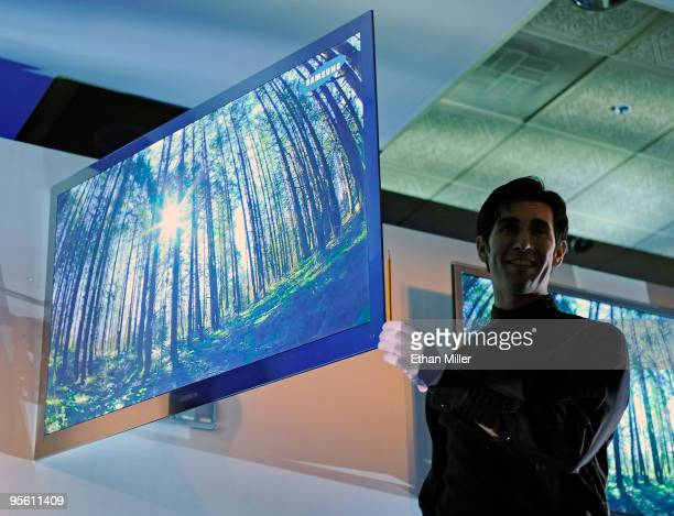 A worker holds a pencil up to the side of the new LED 9000 television by Samsung to show its thickness of less than 3 inches during a press event at...