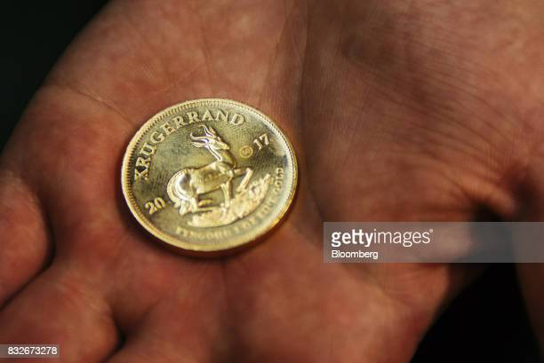 A worker holds a proofed krugerrand gold coin at the Rand Refinery Ltd plant in Germiston South Africa on Wednesday Aug 16 2017 Established by the...