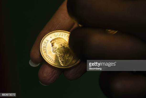 A worker holds a proofed krugerrand gold coin manufactured at the Rand Refinery Ltd plant in Germiston South Africa on Wednesday Aug 16 2017...