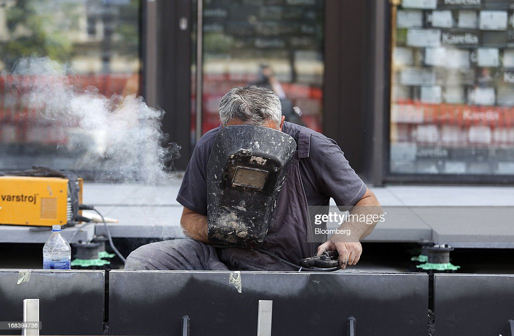 A worker holds a protective mask as he welds metal at a construction site for new residential apartments in Ljubljana, Slovenia, on Wednesday, May 8, 2013. Slovenia's recession will stretch into next year on weak domestic demand as the euro-area country teeters on the brink of needing an international bailout, the European Commission said. Photographer: Chris Ratcliffe/Bloomberg via Getty Images