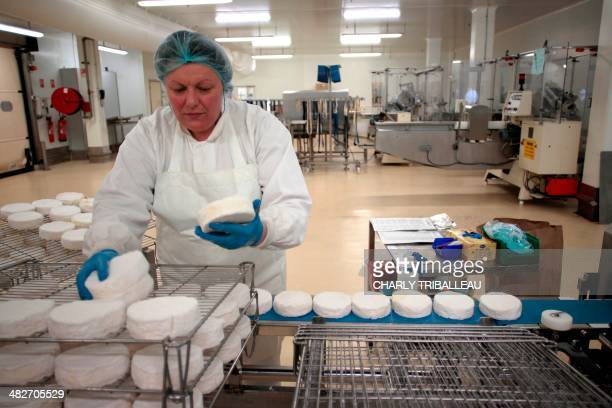 A worker holds a round of French Camembert cheese before it is packaged at the IsignySainteMere dairy cooperative in IsignysurMer northwestern France...