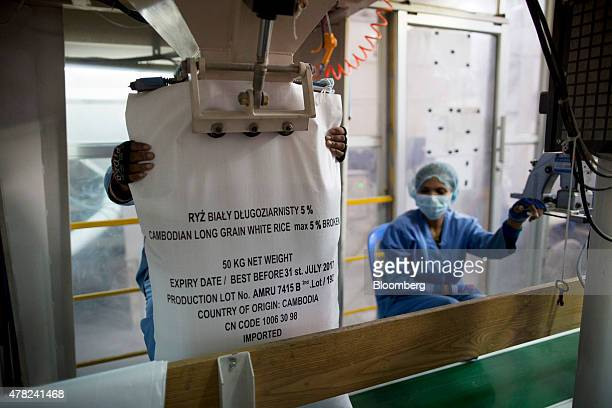 A worker holds a sack up to a machine used to bag rice at the Amru Rice Co processing factory in Phnom Penh Cambodia on Monday June 22 2015 The 10...