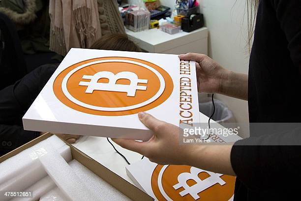 A worker holds a sign at the first bitcoin retail store open in Hong Kong on February 28 2014 in Hong Kong Asia Nexgen a Hong Kong based bitcoin...
