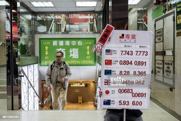 A worker holds a sign listing the exchange rate of the US dollar from top Chinese yuan euro British pound sterling Japanese Yen and Australian dollar...