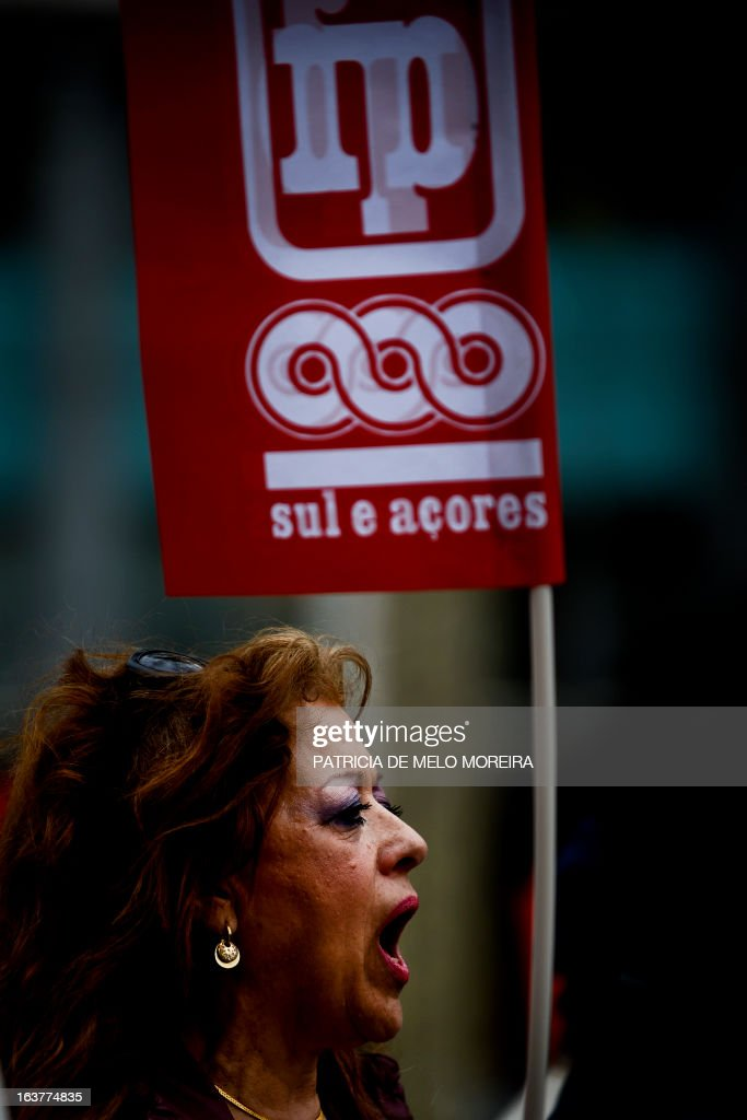 A worker holds a union's flag as she march with thousands of demonstrators during a demonstration called by the unions Common Front, CGTP (General Confederation of the Portuguese Workers) and STAL (National Union of the Local and Regional Public Workers) against the austerity measures of the Portuguese government in Lisbon on March 15, 2013. Today the Finance Minister, Vitor Gaspar, said that the GDP (Gross Domestic Product) will drop 2.3%, that unemployment might reach 19% and the adjustment effort will have to continue for decades.'