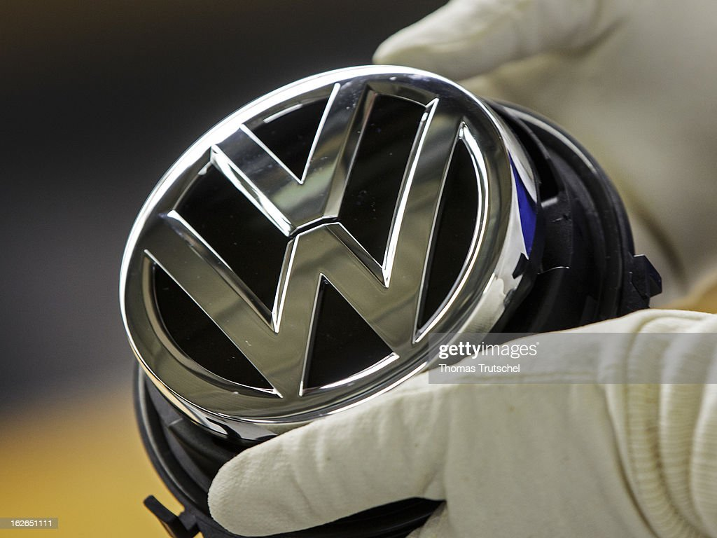 A worker holds a Volkswagen logo at the Volkswagen factory on February 25, 2013 in Wolfsburg, Germany. Volkswagen Aktiengesellschaft announced its key financial data for fiscal year 2012 with sales revenue of EUR 192.7 billion, against the prior year of EUR 159.3 billion. The Group's operating profit of EUR 11.5 billion exceeded the prior-years record level.