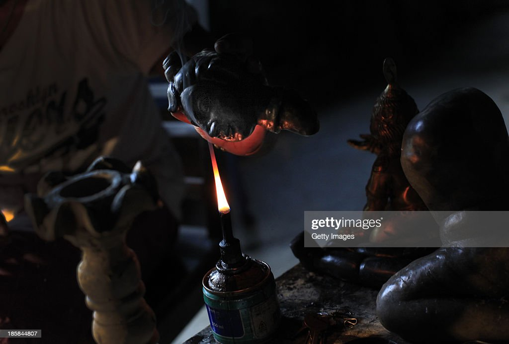 A worker holds a wax sculpture over a candle at Dhamrai Metal Crafts on October 5, 2013 in Dhaka, Bangladesh. The owner of the metal crafts shop, Sukanta Banik, creates bronze sculptures in the art of 'lost wax casting.' The business has been in his family for 200 years. The pieces are first molded in wax, then encased in clay, then baked in the oven, after which metal is poured into the mold. One piece can take up to 10 months to make. The business is suffering because most of these items he creates can now be mass produced in plastic, and as a Hindu artist working in Islamic Bangladesh, the 'depiction of all humans and animals are discouraged by the majority religion.' Recently it took a year and a half to send an order overseas, when Bangladeshi customs held his work in hopes for a bribe.