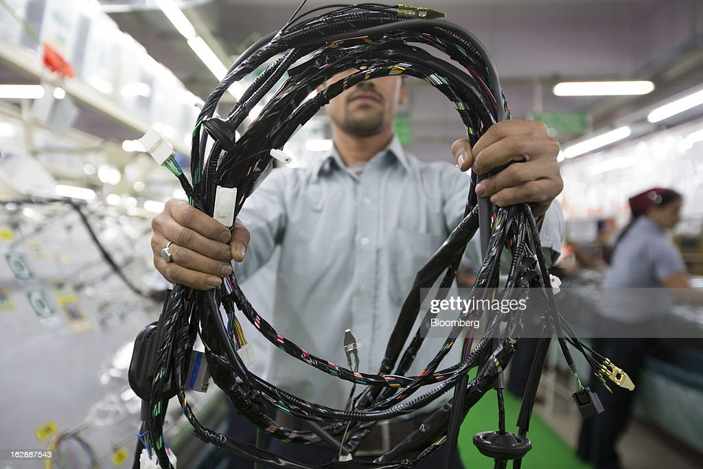 A worker holds a wire harness for a photograph at the Motherson Sumi Systems Ltd. wiring harness plant in Faridabad, India, on Thursday, Feb. 28, 2013. Motherson Sumi Systems Ltd., 25 percent owned by Sumitomo Electric Industries Ltd. and India's biggest auto parts maker, supplies rear view mirrors, bumpers and body panels to clients including Porsche Automobil Holding SE, Bayerische Motoren Werke AG and Volkswagen AG. Photographer: Brent Lewin/Bloomberg via Getty Images