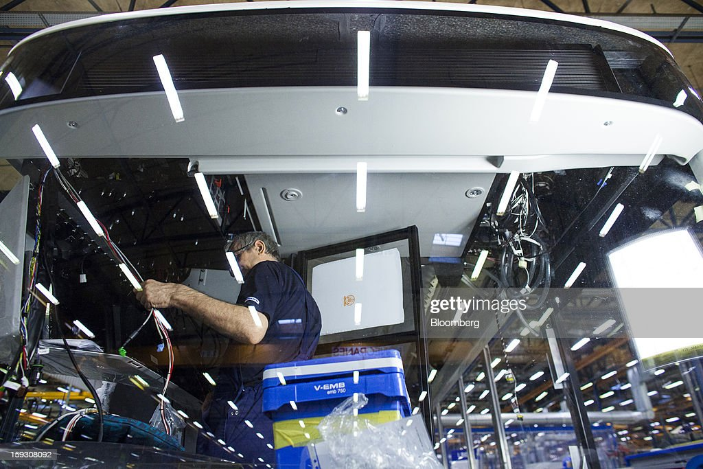 A worker holds a wiring loom inside a bus during assembly at Volvo AB's bus manufacturing plant in Wroclaw, Poland, on Friday, Jan. 11, 2013. Volvo plans to end bus making in Saeffle by June 2013, and will consolidate the business in Europe to its main plant in Wroclaw, Poland, the Gothenburg, Sweden-based company said. Photographer: Bartek Sadowski/Bloomberg via Getty Images