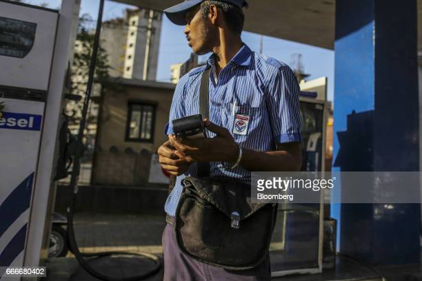 A worker holds an electronic payment terminal at a Hindustan Petroleum Corp gas station in Mumbai India on Saturday April 8 2017 Expanding fuel...