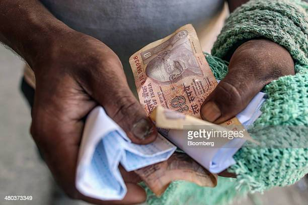 A worker holds Indian ten rupee banknotes at a warehouse in the Vashi Agricultural Produce Market Committee wholesale market in Mumbai India on...