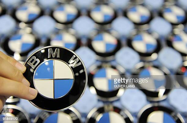 A worker holds up a logo of German carmaker BMW at the company's plant in the southern German city of Dingolfing on October 12 2009 BMW constructs...