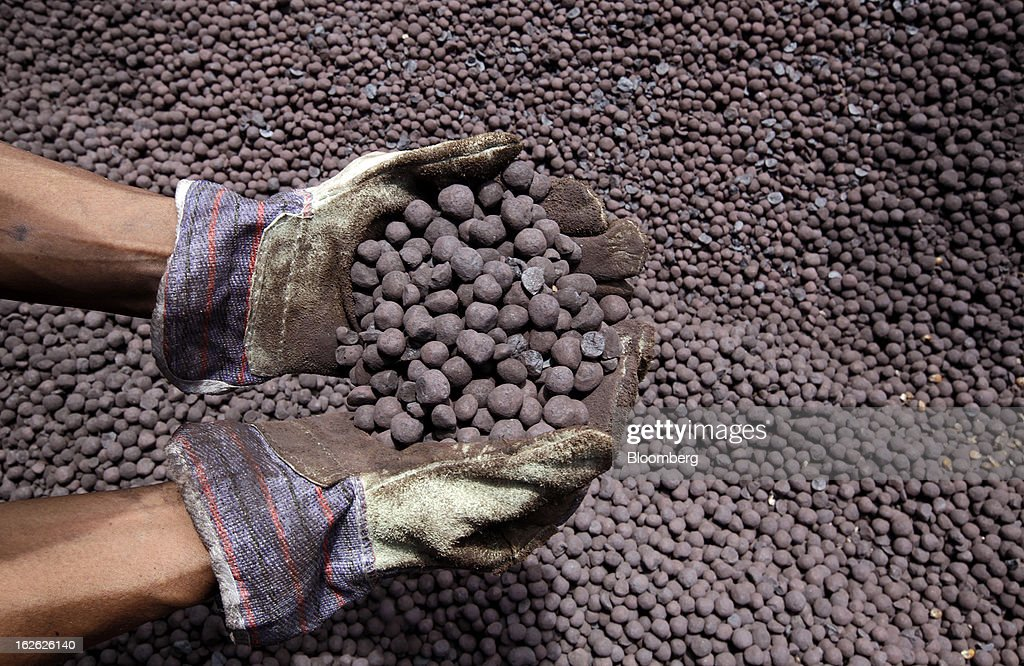 A worker holds up iron ore pellets for a photograph at the Port of Cigading near the PT Krakatau Steel plant in Cilegon, Banten province, Indonesia, on Thursday, Feb. 21, 2013. Krakatau Steel is Indonesia's biggest maker of the metal. Photographer: Dadang Tri/Bloomberg via Getty Images