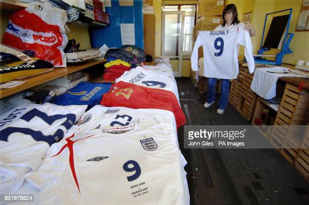 A worker holds up Wayne Rooney's number nine England shirt as she stands with the rest of the team's kit the first batch of which was being collected...