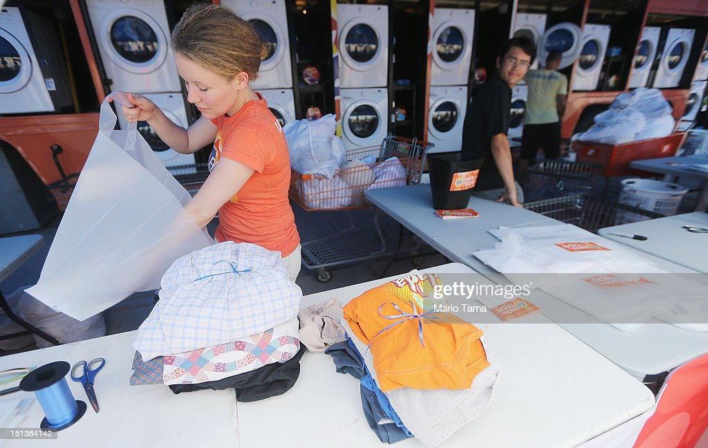 Worker Holly Rochelle sorts a resident's laundry washed for free at the Tide Loads of Hope mobile laundromat set up for those affected by Hurricane Isaac on September 6, 2012 in LaPlace, Louisiana. Louisiana officials estimate that at least 13,000 homes were damaged by Hurricane Isaac.