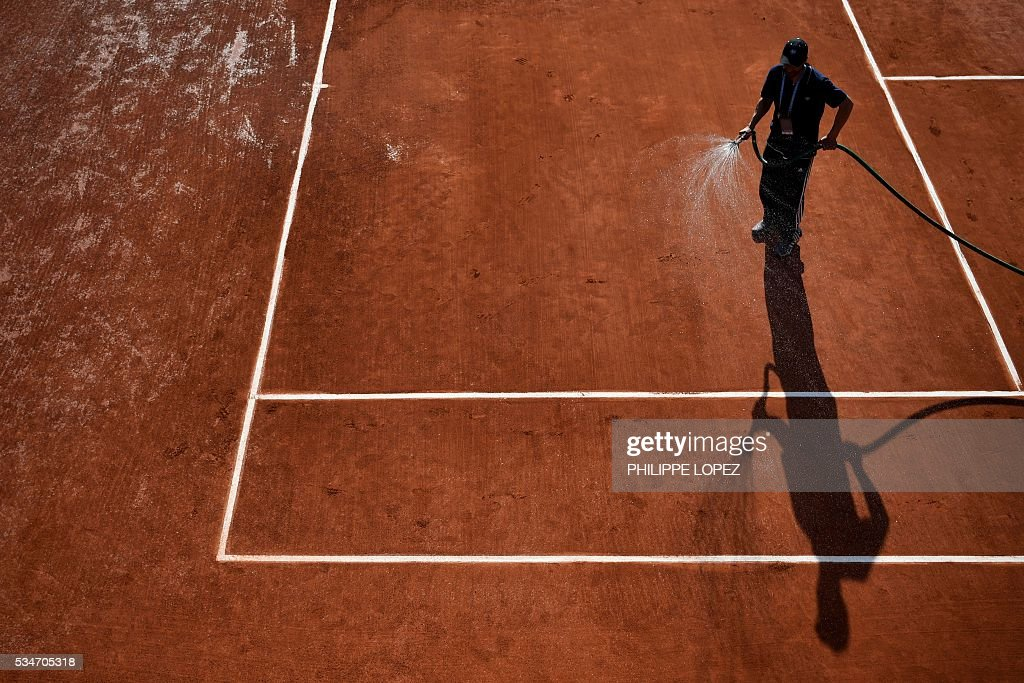 A worker hoses a court at the Roland Garros 2016 French Tennis Open in Paris on May 27, 2016. / AFP / PHILIPPE