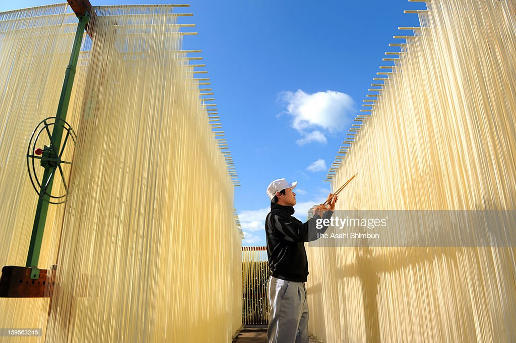 A worker hungs rows of Japanese somen to dry in the winter sun on January 10, 2013 in Tonosho, Kagawa, Japan. The thin wheat noodles forming white curtains and the production at its peak on the island of Shodoshima.